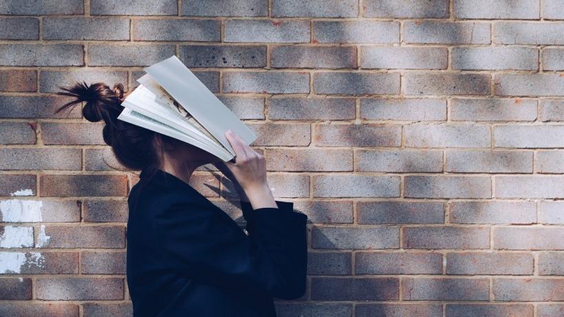 אישה עם ספר על הפנים